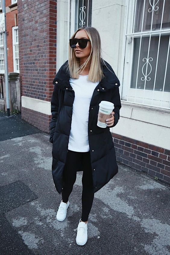 a simple monochromatic look with a white long sleeve top, black leggings, white sneakers and a black puff coat