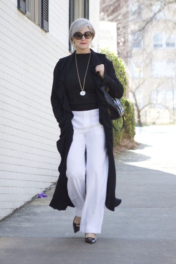 a stylish look with white pants, a black top, black heels, a black bag and a long cardigan