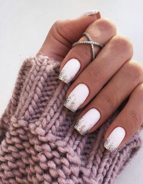 matte white nails with colorful glitter on the tips is a stylish and glam idea