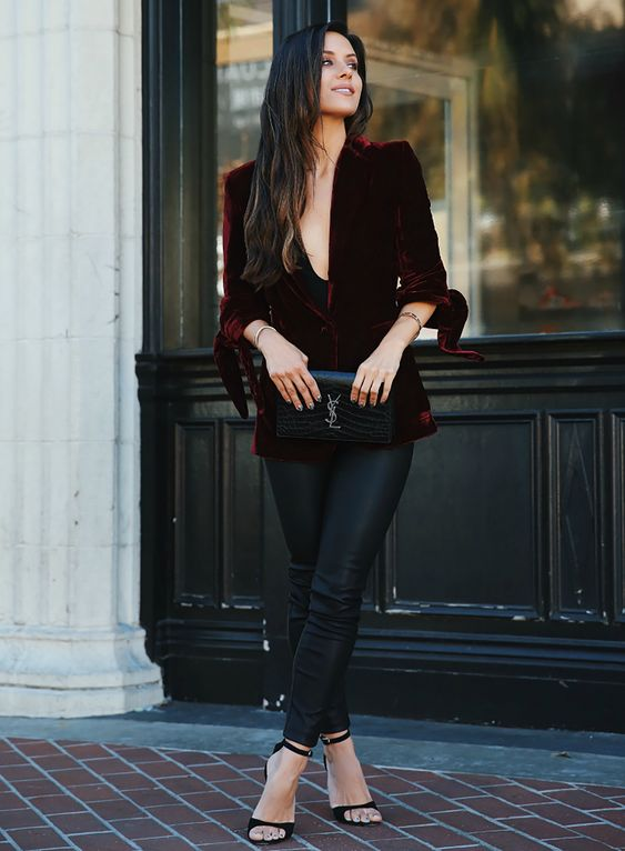 a chic look with a burgundy velvet blazer, black leather pants, black heels and a black bag for a refined touch