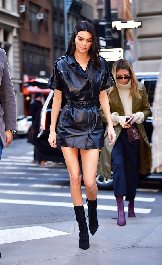 a leather mini dress with a belt and sock boots make a super sexy look for Kylie Jenner
