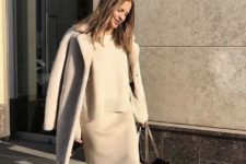 03 a minimalist look with a grey knit suit with a midi skirt, white sneakers and a grey coat plus a brown tote