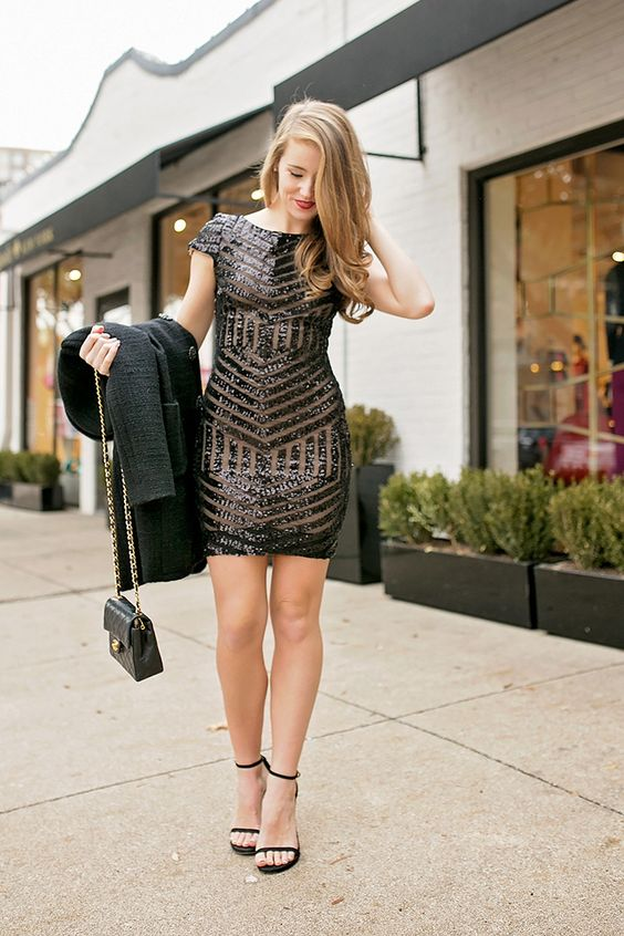 a sparkling black sheath mini dress with a geometric pattern, black heels, a coat and a small bag