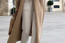 03 a wintry outfit with a white cashmere top, white knit pants, a beige knit cardigan, white boots and a tan bag