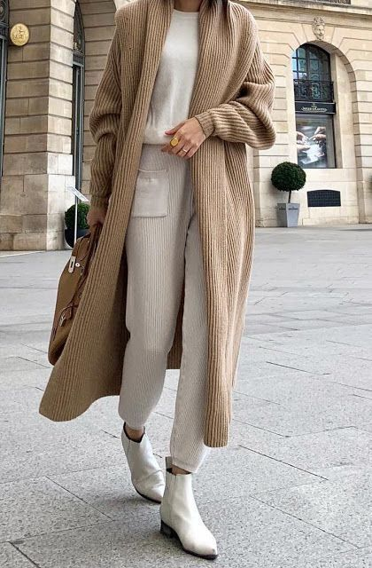 a wintry outfit with a white cashmere top, white knit pants, a beige knit cardigan, white boots and a tan bag