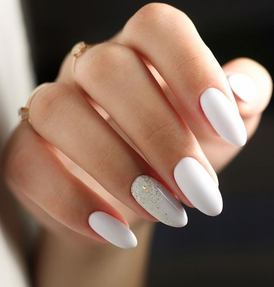 matte white nails with a single nail with metallic glitter that looks spilled on the nail