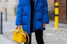 04 a bold outfit with a black top, black jeans, a bold blue padded jacket, a bold yellow bag and black and blue hiking boots