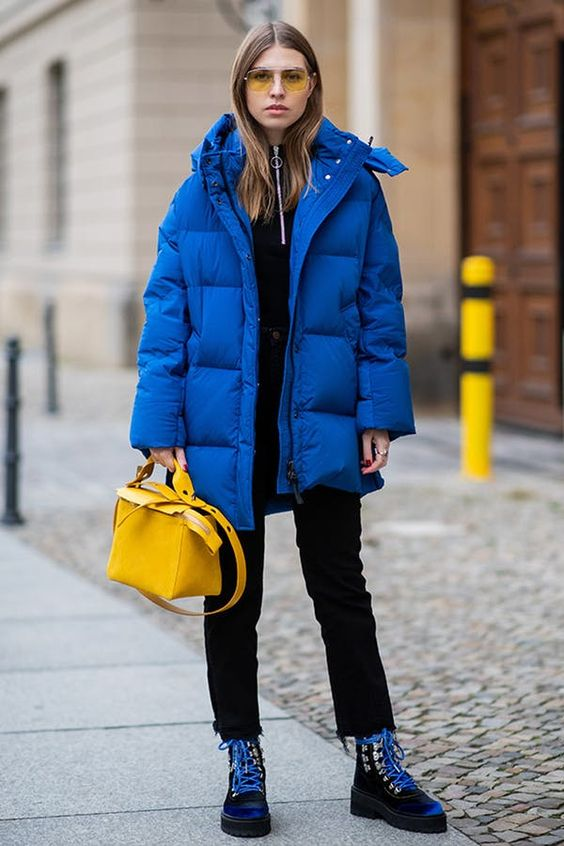 a bold outfit with a black top, black jeans, a bold blue padded jacket, a bold yellow bag and black and blue hiking boots