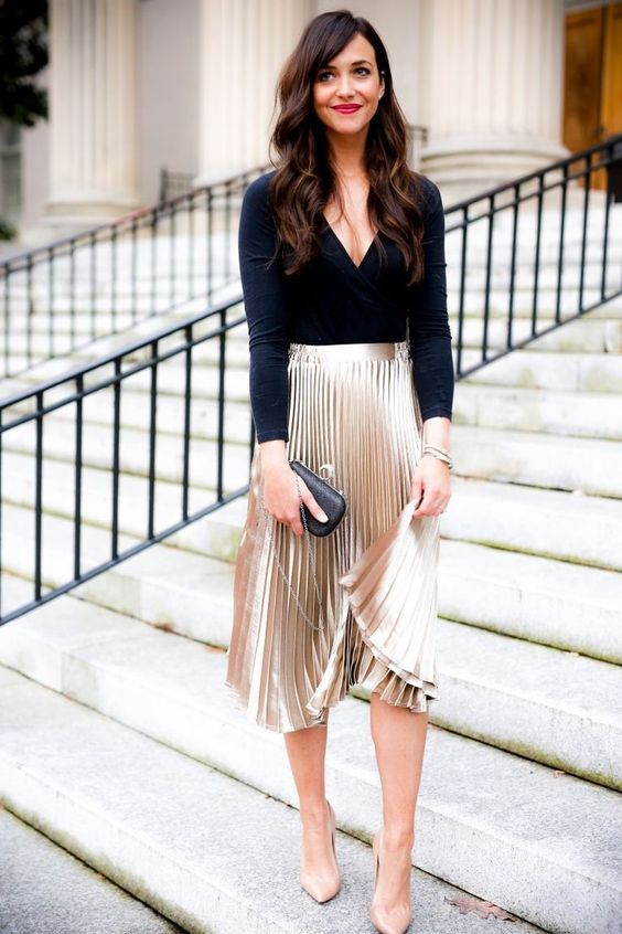 a chic outfit with a black long sleeve top, a metallic pleated midi skirt, nude shoes and a black clutch