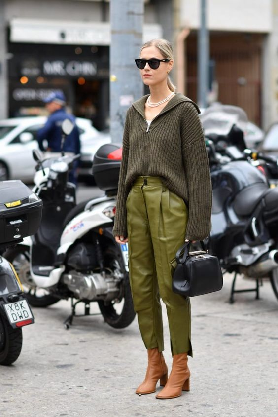 a dark green sweater with a zip, green leather trousers, amber boots and a white top plus a bag