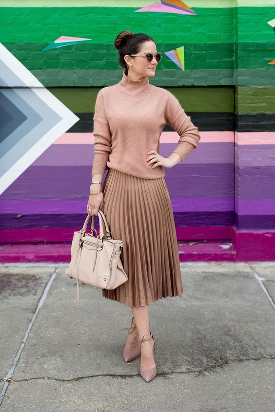 a girlish outfit with a blush pink turtleneck, a bronze pleated midi, blush shoes and a neutral bag