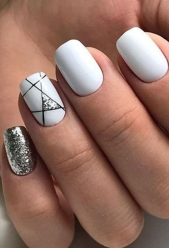 a glossy white manicure with a silver glitter nail and a geometric accent one with black lines