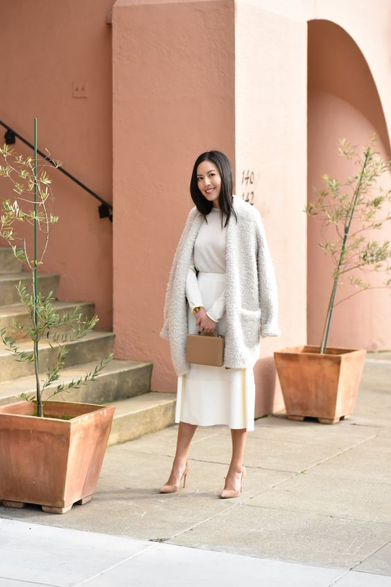 a stylish look with a white A-line skirt, a neutral top, blush shoes, an oversized fluffy cardigan and a tan bag
