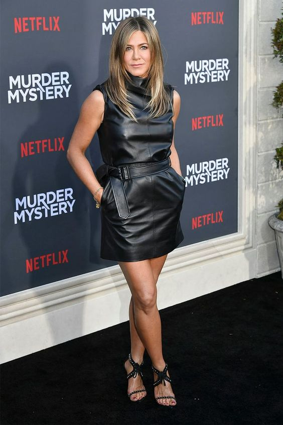 Jennifer Aniston wearing a black leather mini dress with no sleeves and embellished shoes