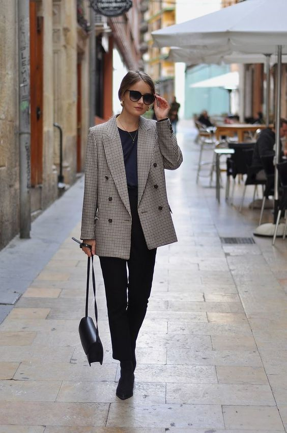 a black long sleeve top, an oversized plaid blazer, black jeans and booties plus a crossbody for a business look
