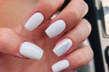 06 a glossy white manicure with a single iridiscent accent nail is a stylish modern idea