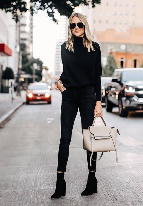a total black look with a turtleneck, cropped skinnies, sock boots, a neutral bag
