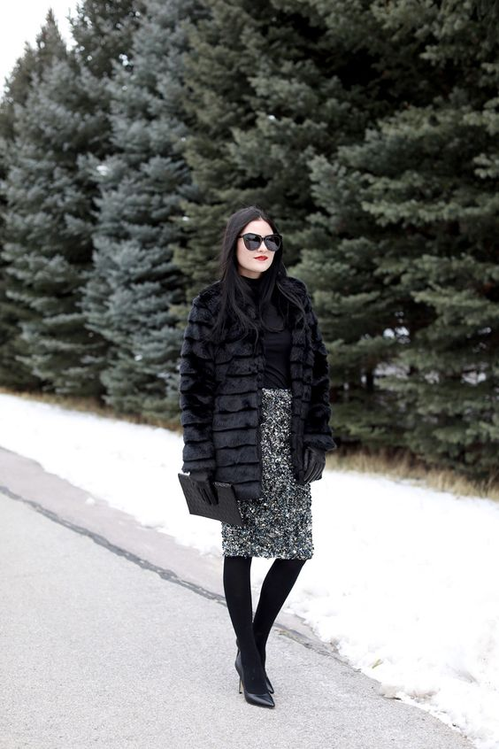 a black top, a black sequin pencil skirt, black tights, black shoes and a faux fur coat plus a clutch