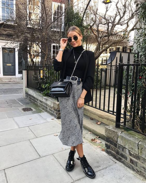 a chic outfit with a black turtleneck, an oversized blazer, a printed midi skirt, black boots and a bag