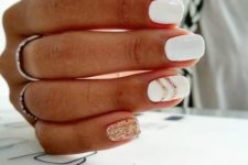 07 a glossy white manicure with copper glitter stripes and a single accent nail looks very festive