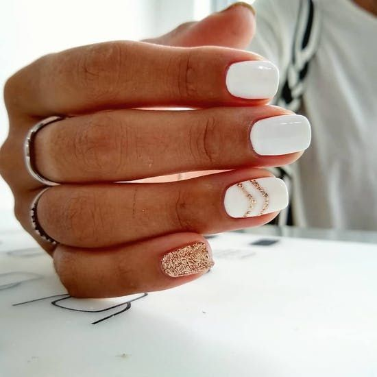 a glossy white manicure with copper glitter stripes and a single accent nail looks very festive