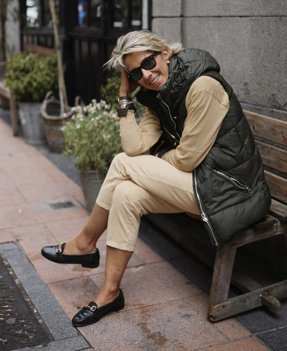 a neutral outfit with a black sporty padded jacket with no sleeves looks fresh and modern