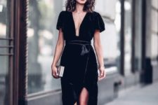 08 a black velvet wrap dress with a plunging neckline and short sleeves, black strappy heels and a metallic clutch
