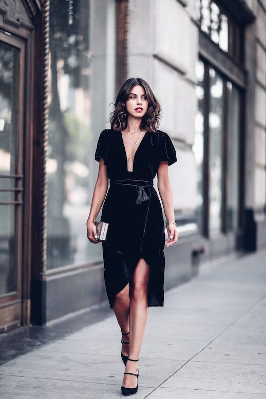 a black velvet wrap dress with a plunging neckline and short sleeves, black strappy heels and a metallic clutch