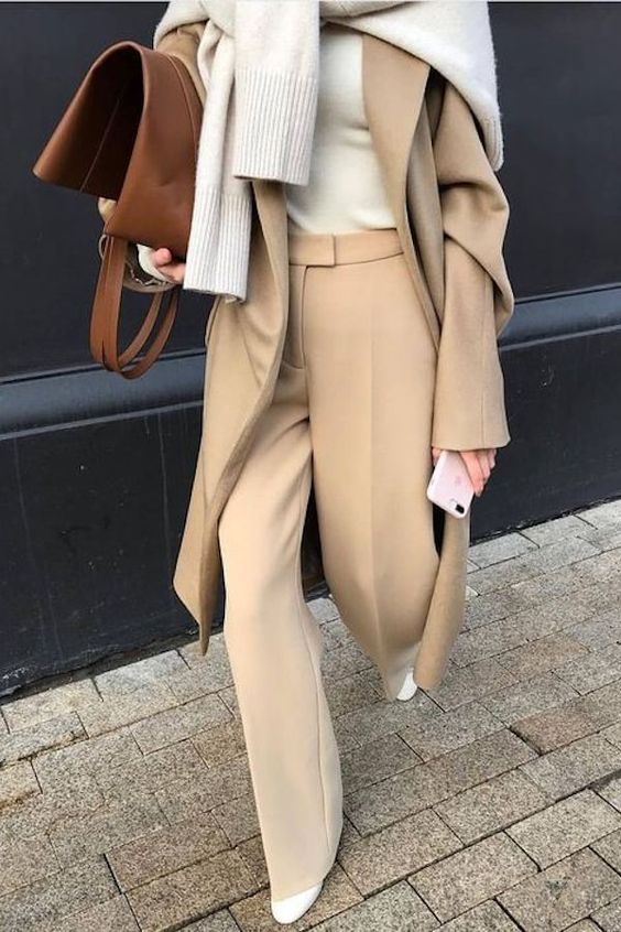 a camel minimalist suit with an oversized blazer, a neutral top and a sweater on top plus a cognac bag