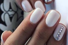 08 a glossy white manicure with sivler glitter accents and a rhinestone stripe on one nail