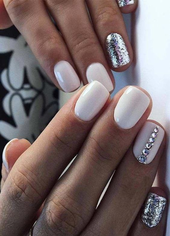 a glossy white manicure with sivler glitter accents and a rhinestone stripe on one nail