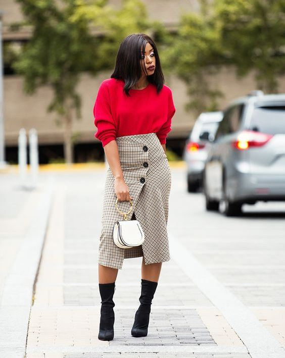 a red oversized jumper, a grey plaid pencil skirt on buttons, black sock boots and a white bag on a ring handle