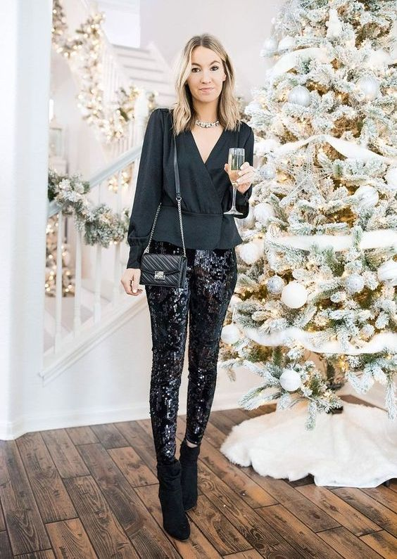 a black peplum top with a V-neckline, black sequin pants, black booties and a small crossbody bag