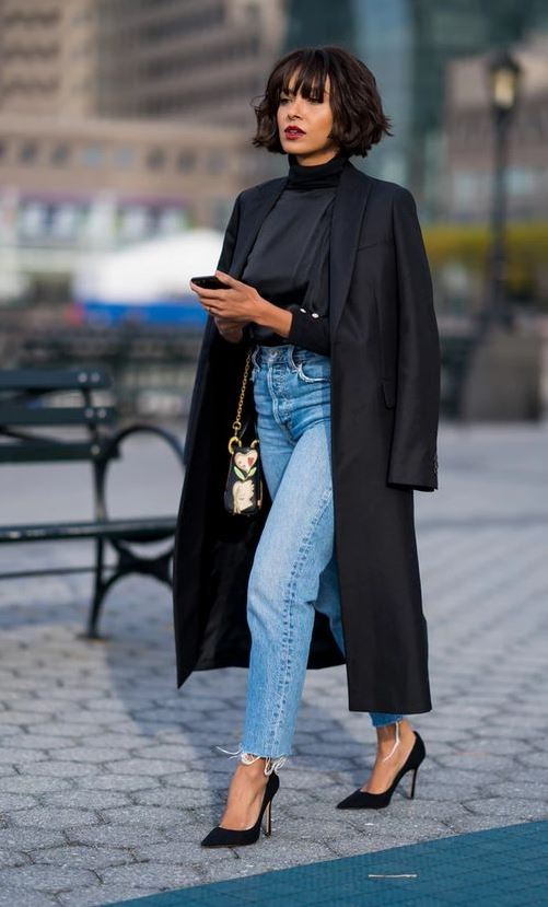 a black turtleneck, blue high waisted straight jeans, black heels and a coat plus a whimsy bag