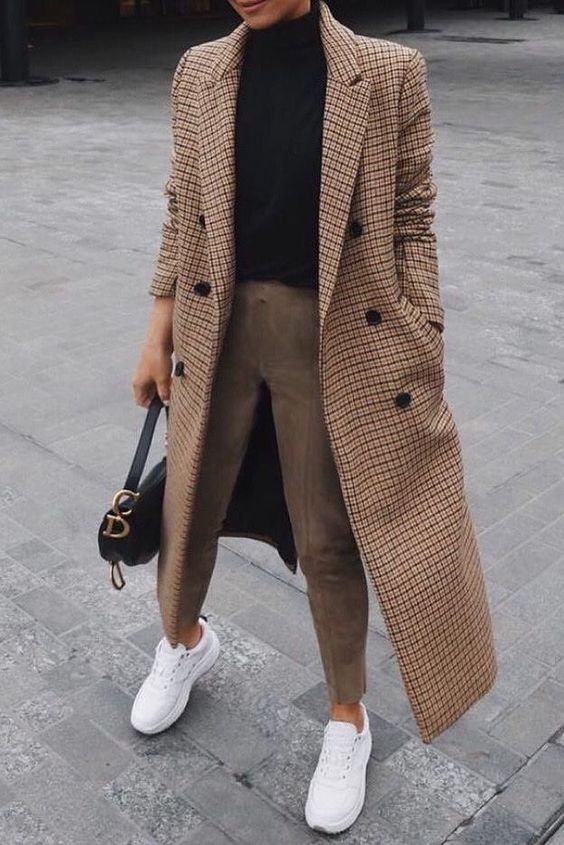 a chic look with a black turtleneck, tan pants, a printed midi coat, white trainers and a black bag