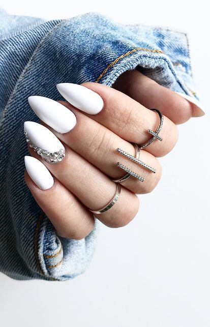 a refined white manicure with a single accent nail with rhinestones looks wow