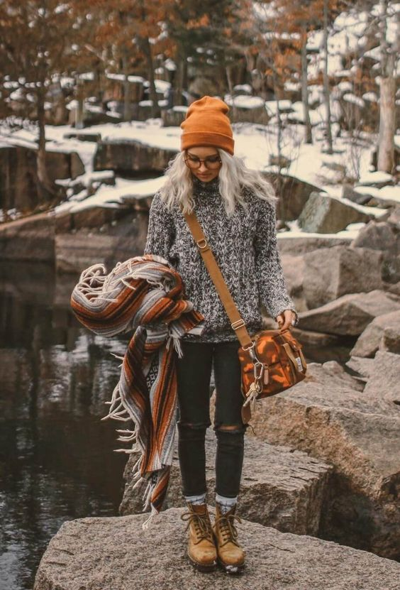 a turtleneck sweater, black ripped skinnies, amber hiking boots, a striped poncho and a mustard beanie