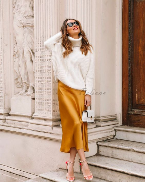 a white oversized sweater, a marigold midi skirt, red embroidered shoes and a small white bag