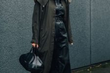 10 a black leather maxi dress worn with a black trench, white sneakers and a dark green bag