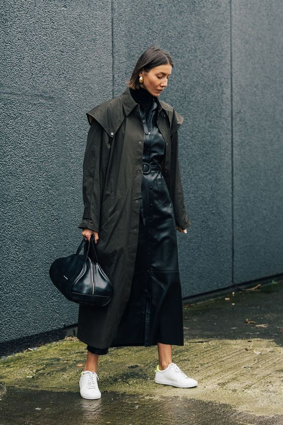 a black leather maxi dress worn with a black trench, white sneakers and a dark green bag
