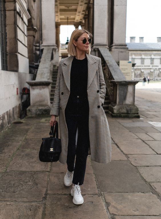 a chic look with a black top, black straight jeans, white sneakers, a printed coat, a black backpack