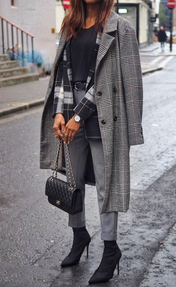 a layered look with a black top, a plaid blazer, grey pants, black sock boots, a black bag and a plaid coat