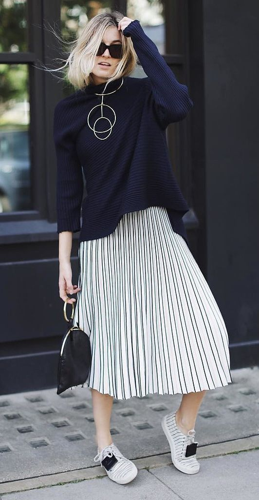 a navy sweater, a striped pleated midi skirt, striped sneakers and statement minimalist accessories