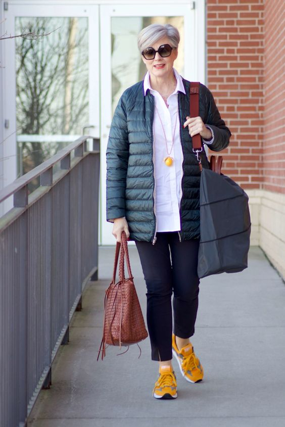 a sporty outfit with a white shirt, black pants, yellow trainers, a black padded jacket and a bright bag