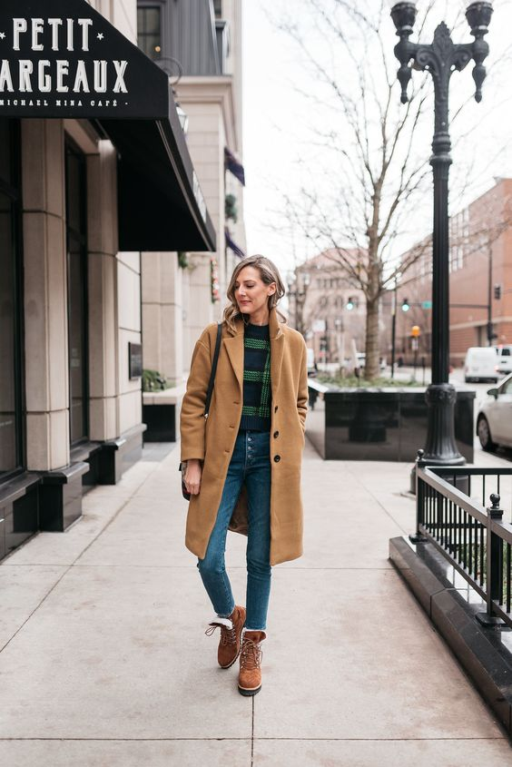 a vintage-infused look with a plaid sweater, blue high waisted jeans, brown hiking boots and a tan coat