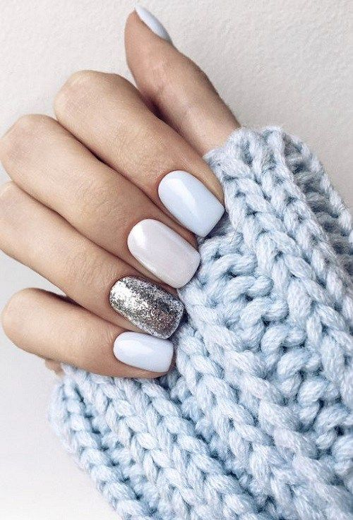 glossy white nails and a single sivler glitter accent one for a shiny and frosty look