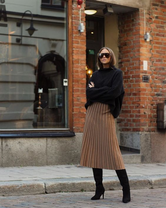 a black oversized sweater, tan pleated midi, black knee boots for a trendy minimal winter look