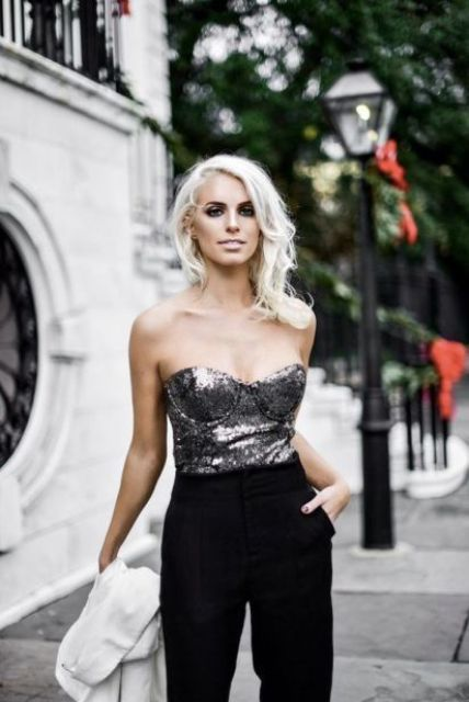 a chic look with a strapless sequin silver top and black velvet trousers plus a white coat