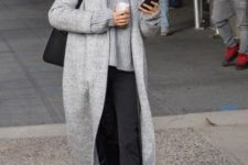 11 a minimalist look with thin striped pants, an oversized grey sweater, black shoes and a grey coat plus a comfy bag
