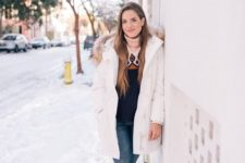11 a vintage-inspired sweater, blue jeans, a white puffed coat and hiking boots for snowy winter